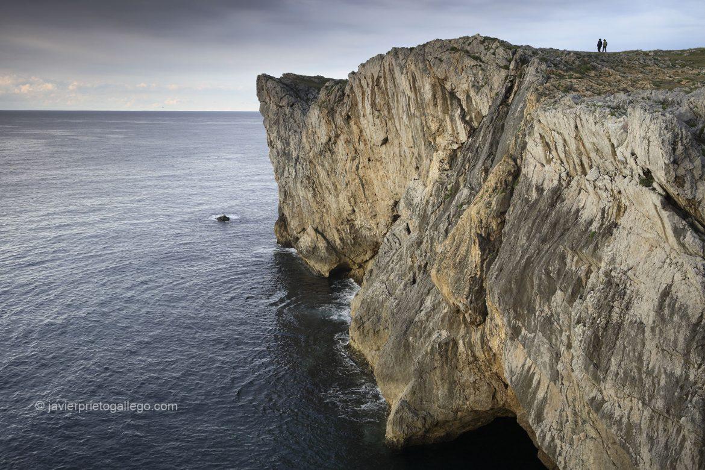 Dos personas pasean junto a los acantilados en los Bufones de Pría. Mar Cantábrico. Llanes. Asturias. España © Javier Prieto Gallego