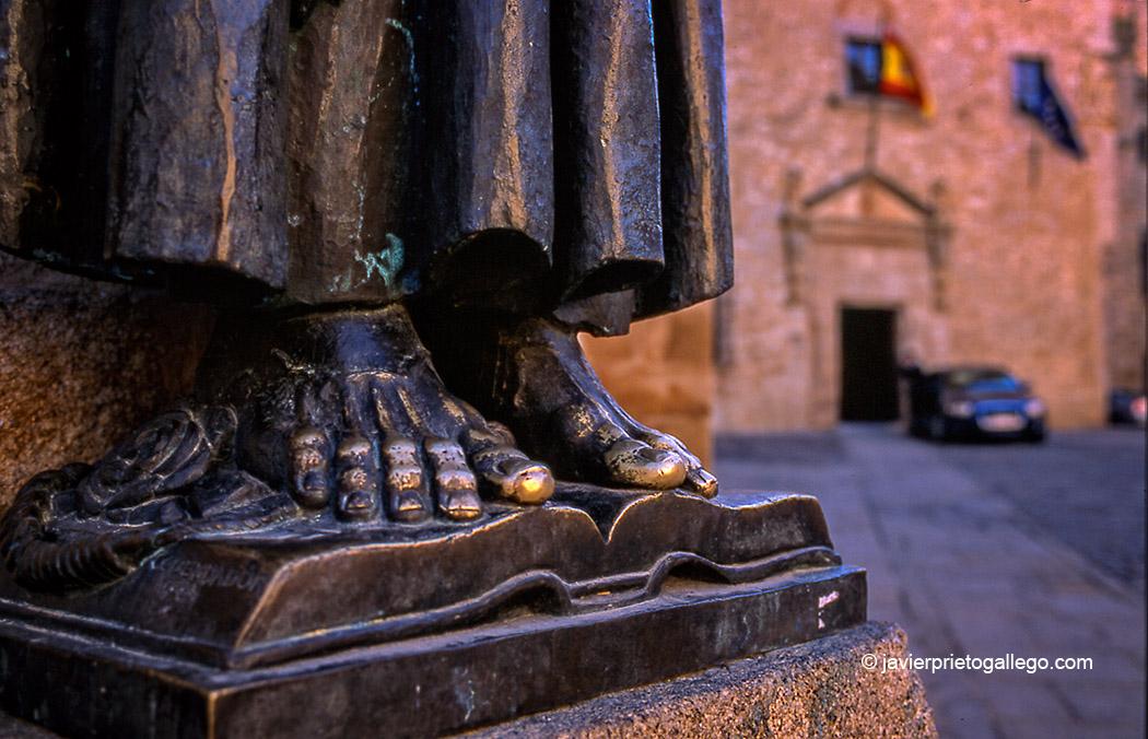Estatua de San Pedro de Alcántara (plaza de Santa María, en Cáceres). Realizada por Enrique Pérez Comendador en 1954. Bronce sobre pedestal de granito. Se comenta que la imagen del Santo es un autorretrato del propio escultor. El pulido que tienen los pies es debido a las continuas muestras de devoción de los creyentes que, en un acto de adoración y respeto, besan los pies de la escultura. Al fondo de la imagen, coches oficiales de la Junta de Extremadura. [Cáceres. Extremadura. España. © Javier Prieto Gallego